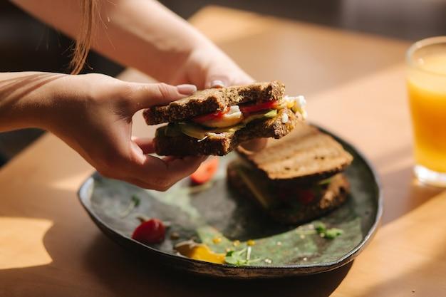 Женщина держит в руках укушенный бутерброд. ржаной тост с авокадо. свежий апельсиновый сок веганское питание.
