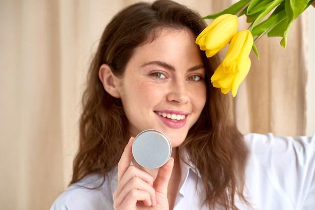 Женщина держит банку с косметическим продуктом в руке с желтыми тюльпанами и бежевым фоном занавеса