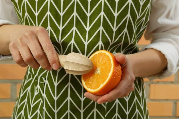 Женщина держит соковыжималку и апельсин на фоне кирпичной стены