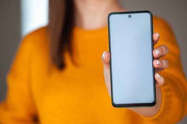 여자는 주황색 스웨터에 손에 휴대 전화 화면 모형을 개최