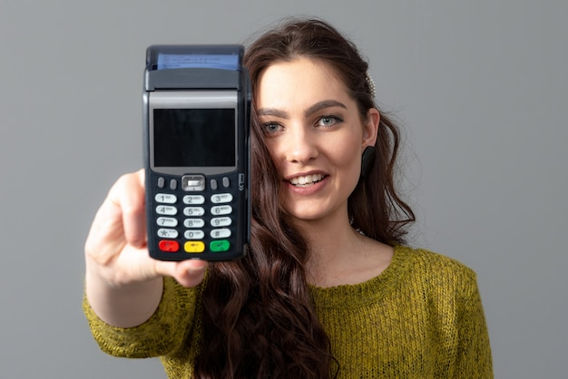 Woman hold modern bank payment terminal to process acquire credit card payments, lifestyle concept