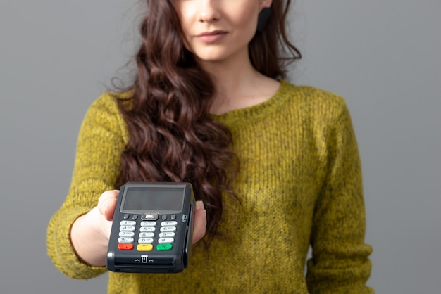 Woman hold modern bank payment terminal to process acquire credit card payments