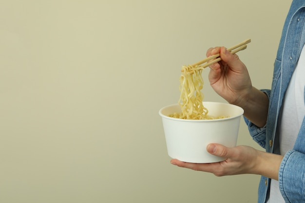 Woman hold paper bowl and chopsticks with noodles, space for text
