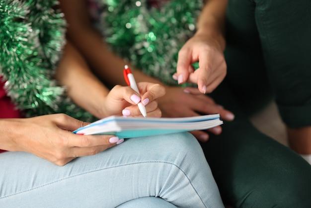 女性はペンを手に持ってノートに書きます。