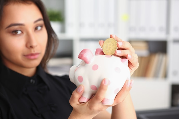 Woman hold piggybank in arms put money into moneybox