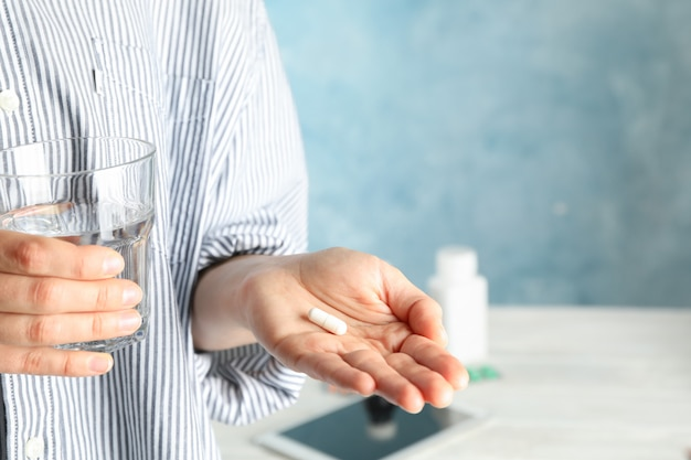 Woman hold pill and glass of water