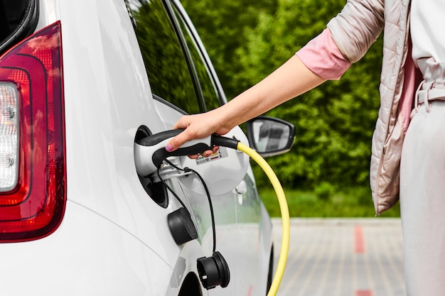 Woman hold power supply plugged into an electric car at public charging station outdoors.