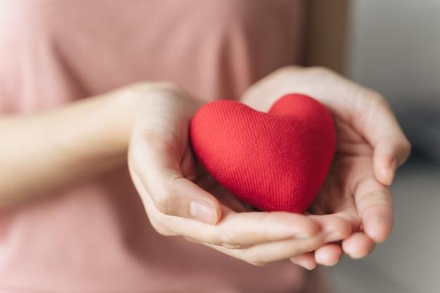Женщина держит красное сердце любовь пожертвование медицинского страхования счастливый благотворительный день добровольца психического здоровья