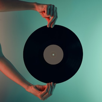 Woman hold retro vinyl disc in hands toned photo