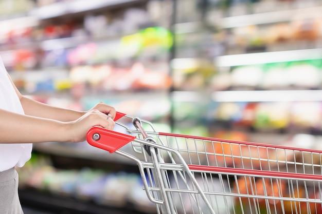 女性は抽象的なぼかしのスーパーマーケットのディスカウントストアの通路と製品の棚のインテリアの焦点がぼけたボケ味の背景でショッピングカートを保持します