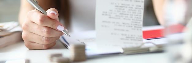 Женщина держит серебряную ручку и чек в руке