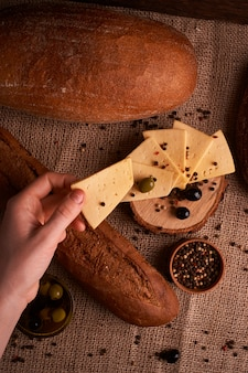 Woman hold slice of traditional dutch semi hard cheese on olives, bread and baguette.