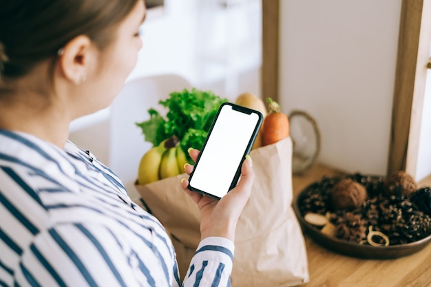 Woman hold the smartphone with white screen, mock up. online food market concept.