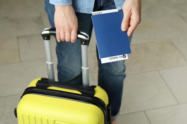 Женщина держит чемодан и паспорт с билетом и covid - 19 марок