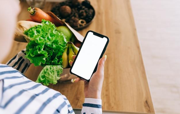 여자는 흰색 화면으로 스마트 폰을 잡고, 모의. 온라인 식품 시장 개념.