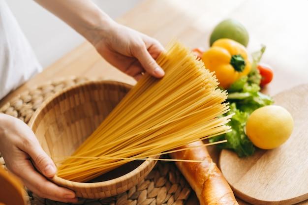 女性は手に小麦スパゲッティパスタを保持します