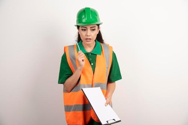La donna tiene il bordo vuoto bianco di affari vestito in uniforme del costruttore. foto di alta qualità