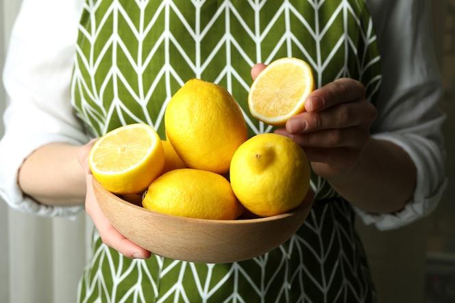 ciotola di legno della stretta della donna con i limoni maturi