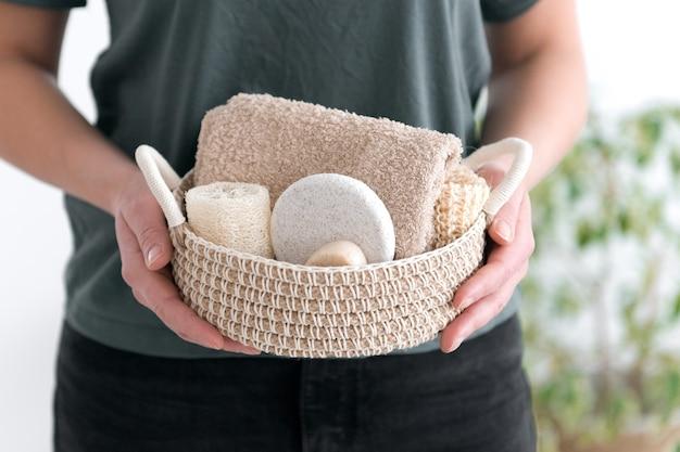 女性は自然なボディケア製品で編まれたバスケットを保持します