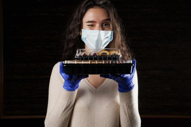 장갑과 얼굴 마스크를 사용하여 손에 2 개의 초밥 상자를 들고 여자