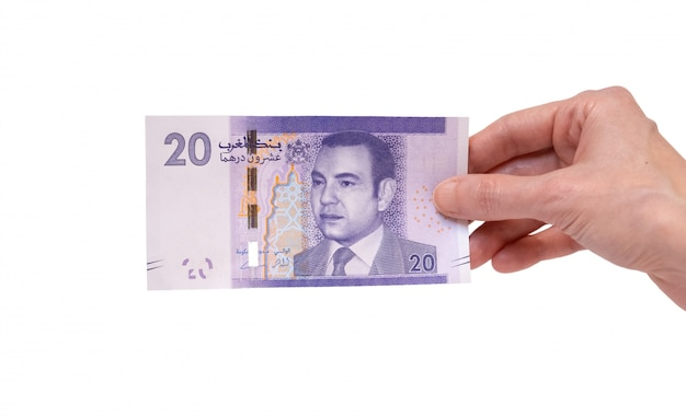 Woman holding a 20 moroccon dirham banknote in her hand on a white