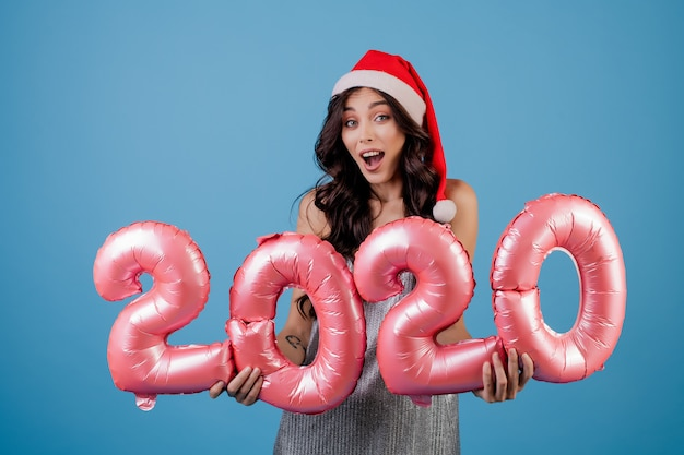 Woman holding 2020 new year balloons wearing christmas hat and dress