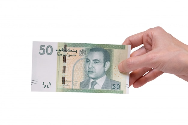 Woman holding a 50 moroccon dirham banknote in her hand on a white