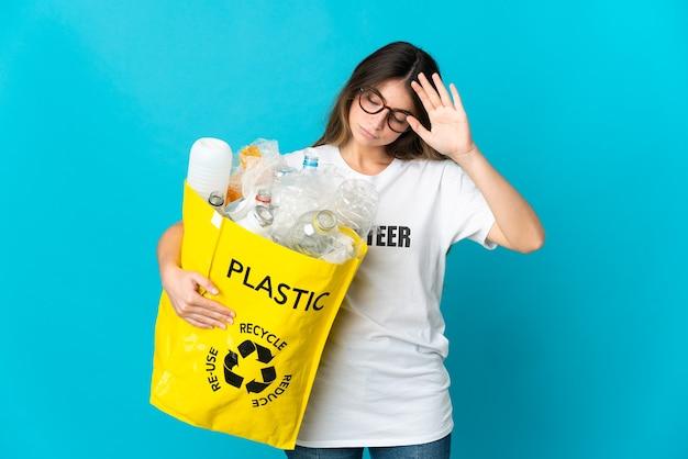 Женщина, держащая сумку, полную бутылок для переработки, изолирована на синем, делая жест стоп и разочарована