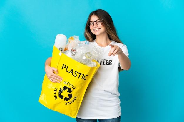 Женщина, держащая сумку, полную бутылок для переработки, изолирована на синем указательном фронте со счастливым выражением лица