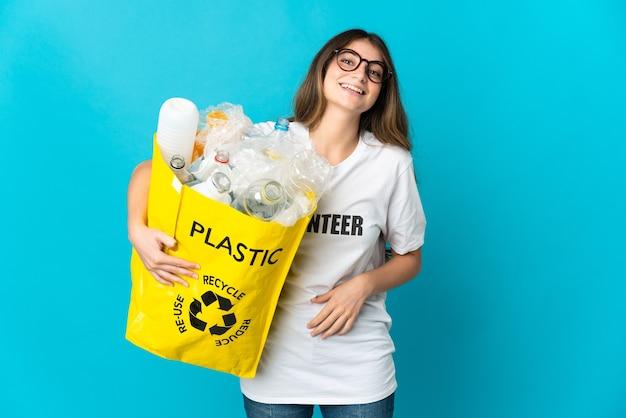 たくさんの笑顔で青に孤立してリサイクルするためにボトルでいっぱいのバッグを持っている女性