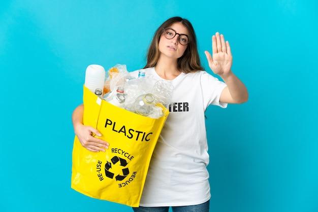 停止ジェスチャーを作る青い壁に隔離されたリサイクルするためにボトルでいっぱいのバッグを保持している女性