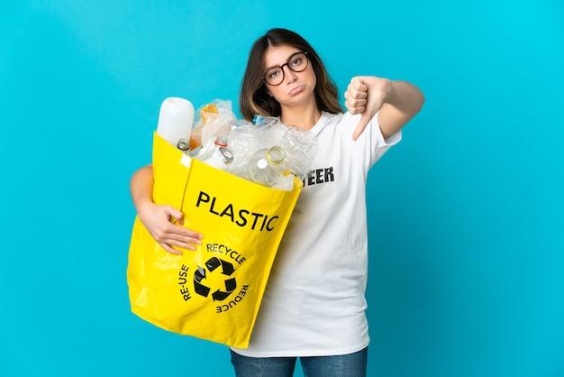 否定的な表現で親指を下に示す青い壁に隔離されたリサイクルするためにボトルでいっぱいのバッグを保持している女性