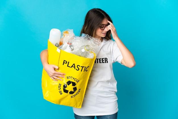 青い笑いでリサイクルするためにボトルでいっぱいのバッグを持っている女性