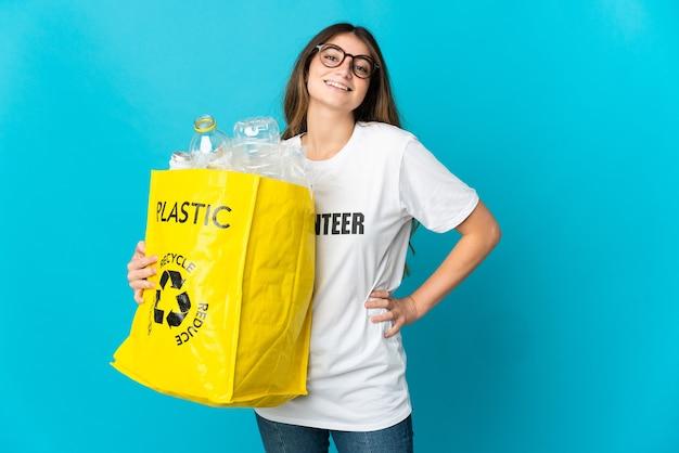 腰に腕を組んで笑顔で青いポーズでリサイクルするためにボトルでいっぱいのバッグを持っている女性