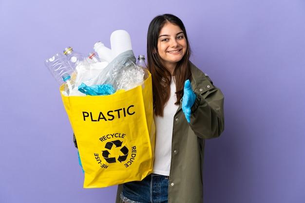 Женщина держит мешок, полный пластиковых бутылок для переработки