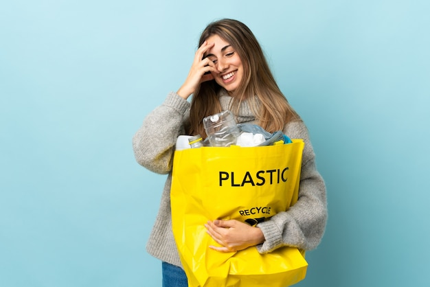 Женщина держит мешок, полный пластиковых бутылок