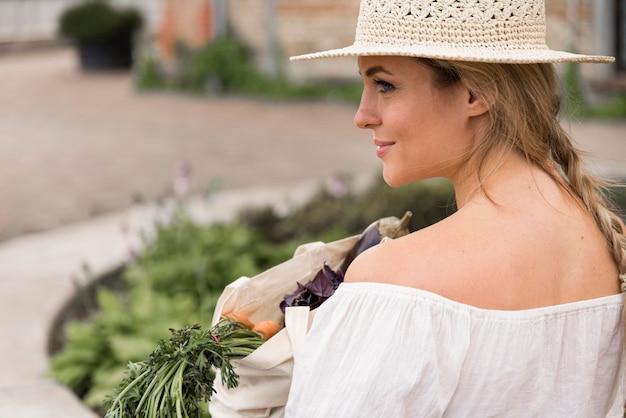 Женщина держит мешок овощей через плечо