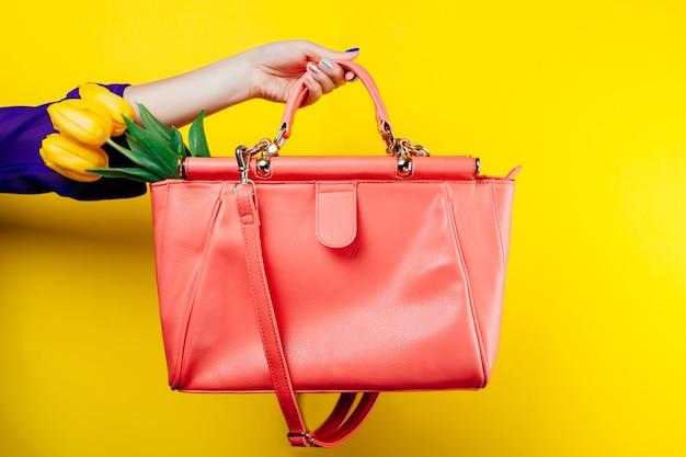 Женщина держит сумку с желтыми тюльпанами