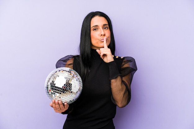 秘密を保持するか、沈黙を求めて紫色の背景で隔離のボールパーティーを保持している女性。