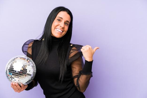 親指の指を離れて、笑ってのんきな紫色の点で隔離のボールパーティーを保持している女性。