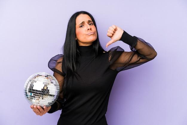 嫌いなジェスチャーを示す紫色に分離されたボールパーティーを保持している女性、親指を下に