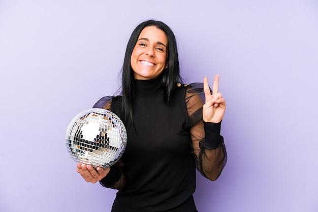 指で2番目を示す紫色で隔離のボールパーティーを保持している女性。