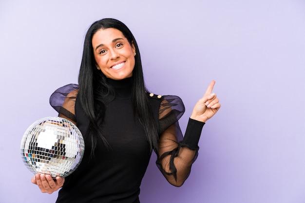 紫色の笑顔と脇を指して、空白のスペースで何かを見せて孤立したボールパーティーを保持している女性。