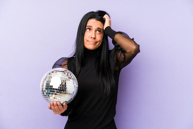 Женщина, держащая мяч на фиолетовой стене в шоке, вспомнила важную встречу.