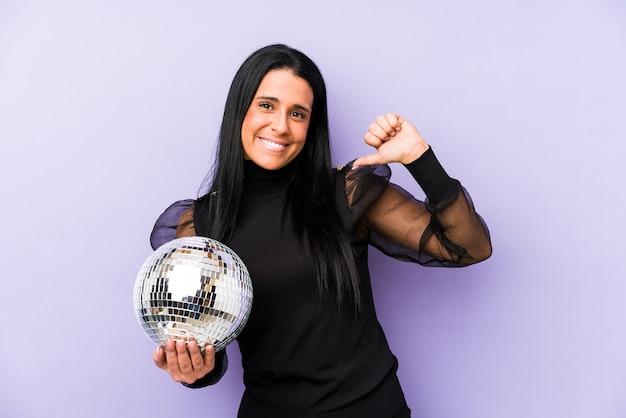 Женщина, держащая вечеринку с мячом на фиолетовой стене, чувствует себя гордой и уверенной в себе, примером для подражания.