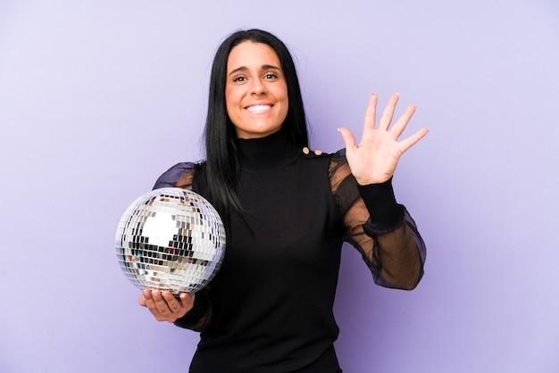 Женщина, держащая партию с мячом, изолированная на фиолетовой стене, улыбается веселый, показывая номер пять с пальцами.