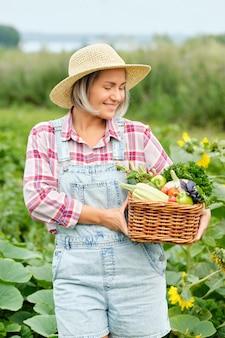 有機バイオファームで収穫有機野菜と根でいっぱいのバスケットを持っている女性。秋の野菜の収穫。