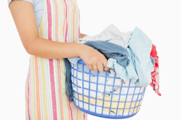洗濯物でいっぱいのバスケットを持っている女性