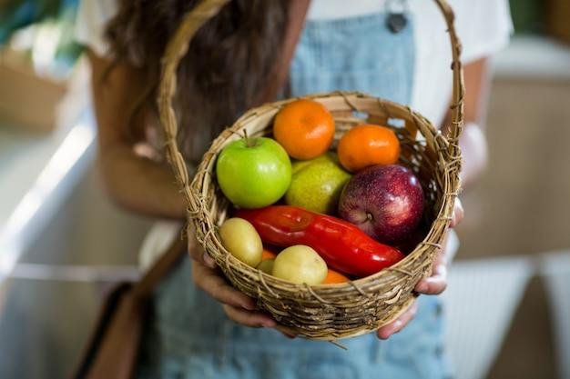 Женщина держит корзину фруктов и овощей в продуктовом магазине