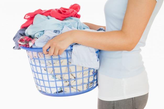 洗濯物のあふれたバスケットを持っている女性